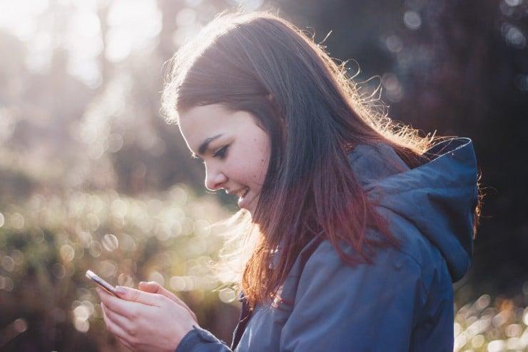 Opiskelija tekee tehtäviä puhelin kädessä